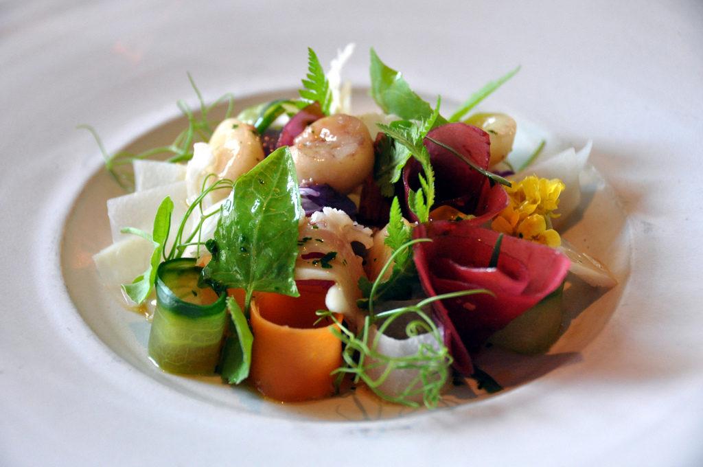 Salada dinamarquesa com legumes variados, incluindo castanhas d'água, milho e fatias finas de cenoura e pepino